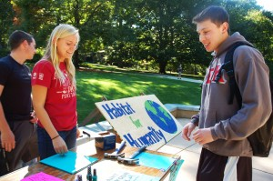 Karen Konkoly, '17, president of Habitat for Humaniy club, and Matt Faller, '17, discuss what nail polish to add to the nail on Tuesday, Oct. 6 2015, at the UC Front Lawn. The participation of the event only cost two dollars to hammer and paint a nail which all nail polish was donated by board members of the club. (Madison Hoff/B&W photo)