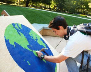 Eric Mcmillan, '18, hammers a nail into the world mural for donating two dollars to the fundraiser held on Tuesday, Oct. 6 2015, at the UC Front Lawn. Eric decided to place his nail in South America, but other common places people chose to put their nails were in Africa, parts of Europe, and the East Coast of the United States. (Madison Hoff/B&W photo)