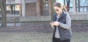 Emma Fitzsimmons, '19, walking through the Lower Centennial quad checking her social media pages on her phone on Sunday, Feb. 28, 2016. Professor Janey Lee conducted research on whether or not social media can change your mind. (Madi Welker/B&W Staff)