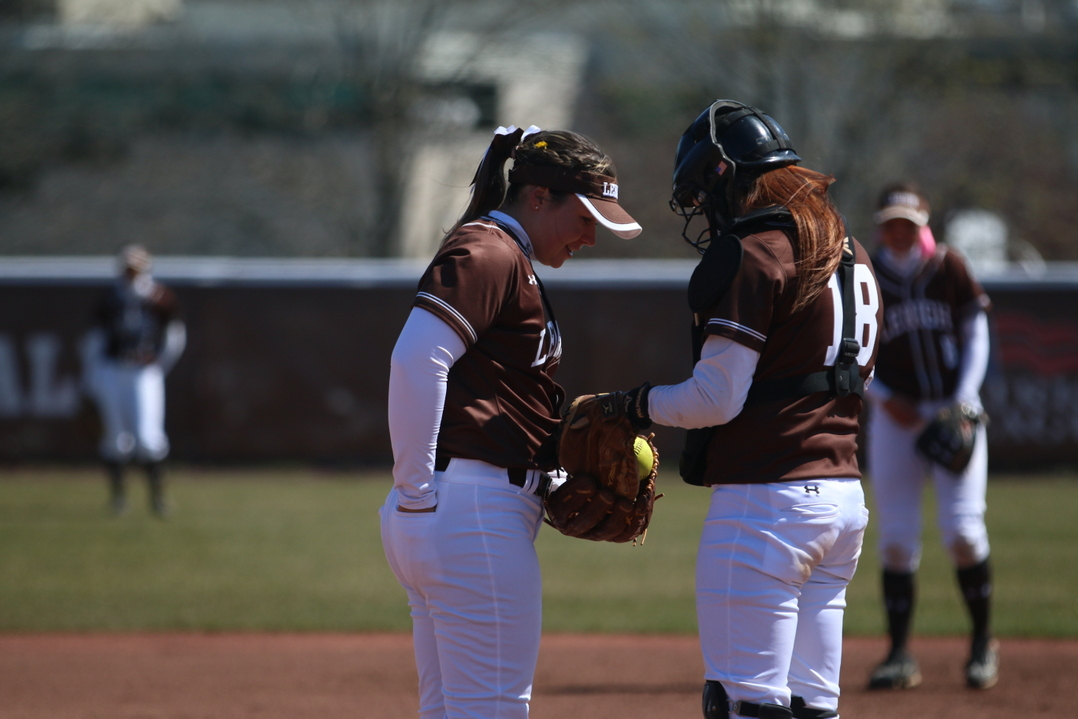 Junior pitcher Christine Campbell talks with senior catcher Carissa Zito between pitches of the second game of a double header against Colgate University on Sunday, April 10, 2016, at Leadership Park. Campbell said having Zito behind the plate has helped her progress and succeed over the past year. (Erik Thomas/B&W Photo)