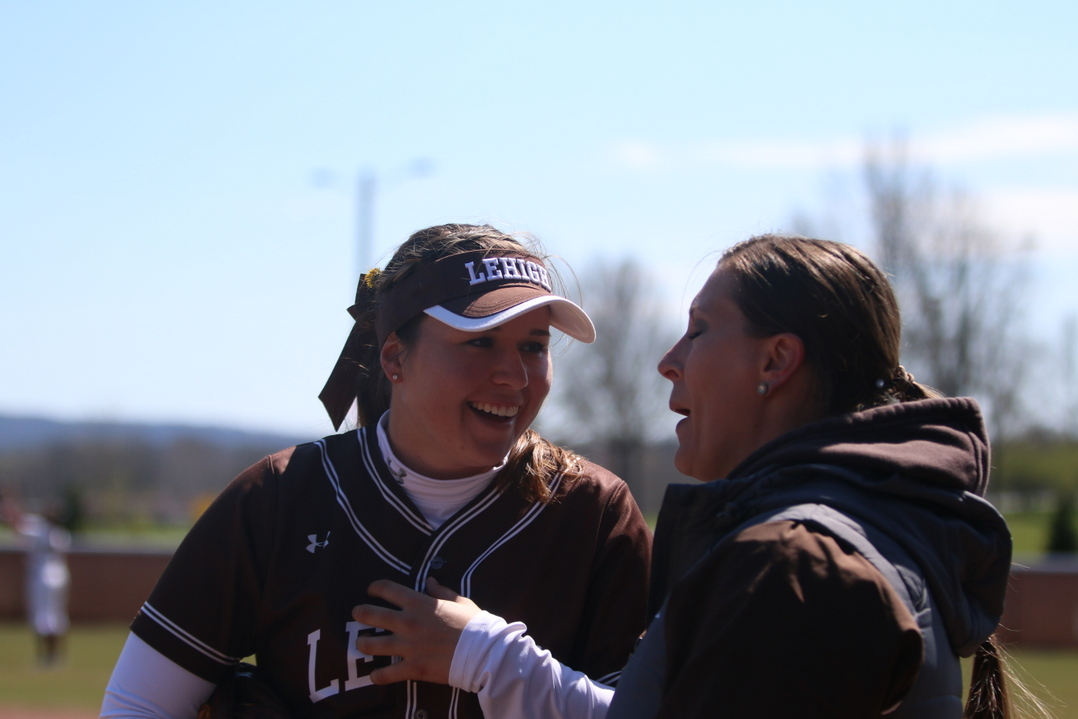 Junior pitcher Christine Campbell talks with assistant coach Stephanie Covelle between innings of the second game of a double header against Colgate University on Sunday, April 10, 2016, at Leadership Park. Covelle has been the pitching coach for Lehigh softball for 12 years this season. (Erik Thomas/B&W Photo)