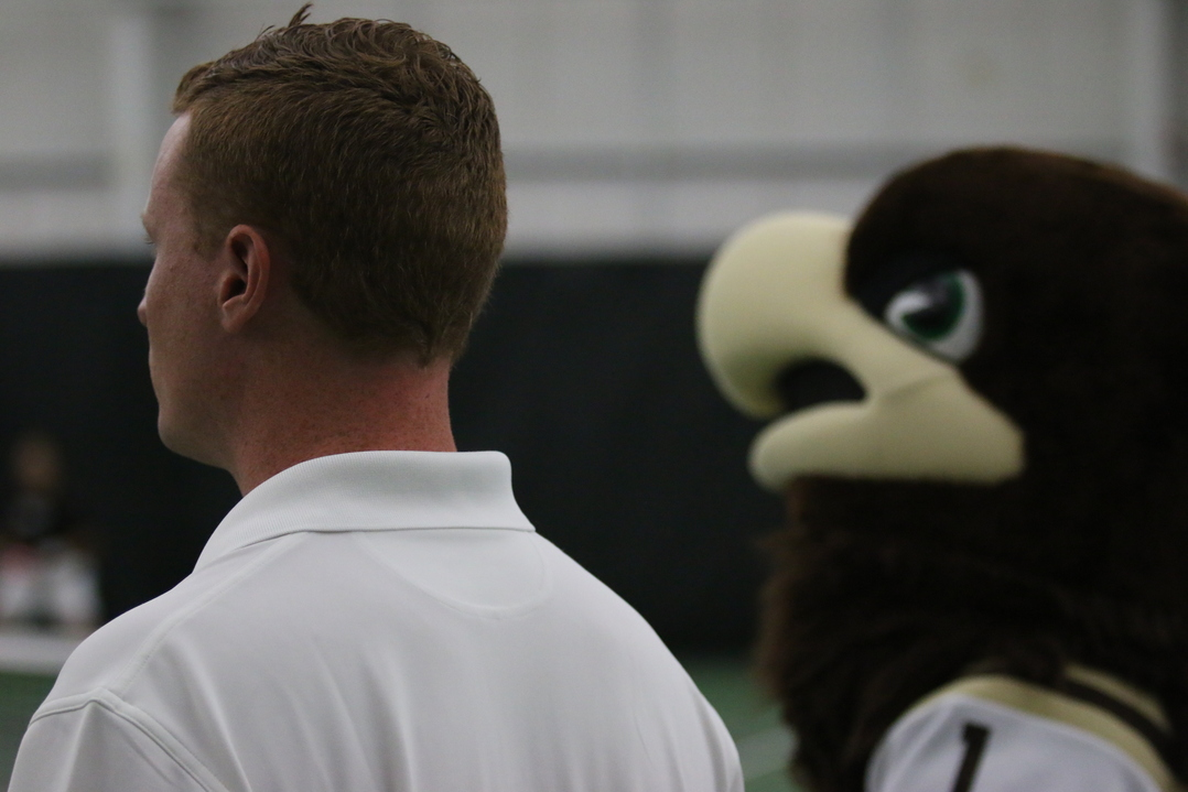 Lehigh men's tennis coach Wouter Hendrix looks on alongside Mountain Hawk mascot Clutch as his team competes in the Patriot League quarterfinals against Colgate University on Friday, April 29, 2016, at the Lewis Tennis Center. Hendrix's team came into the tournament as the No. 5 seed.