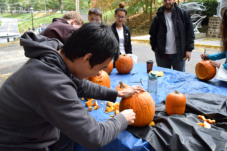Kaung Myat, '19, takes part in the pumpkin carving at Psi Upsilon on Sunday, Oct. 23, 2016. Lehigh students carved out what the children designed on their pumpkins for Spooktacular. (Malcolm Scobell/B&W staff)
