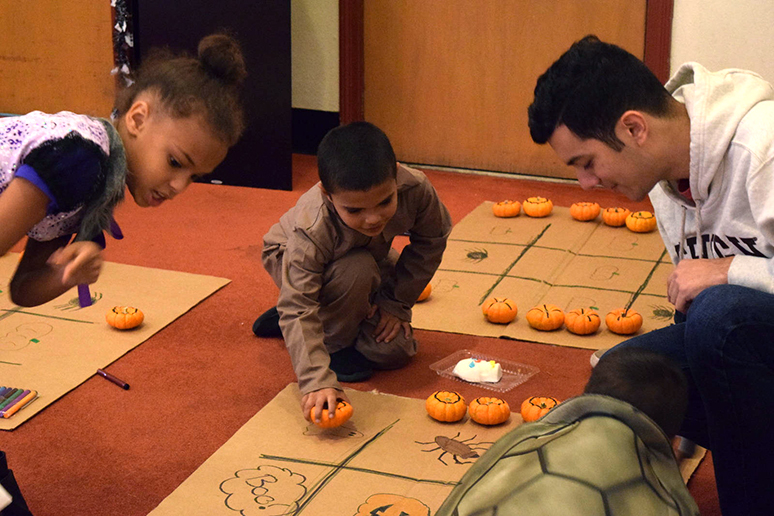 Steven Badillo, '19, teaches trick-or-treaters how to play tic tac toe in the University Center on Sunday, Oct, 23, 2016. Many local Bethlehem families brought their children to Spooktacular where there were plenty of activities for the children. (Malcolm Scobell/B&W staff)
