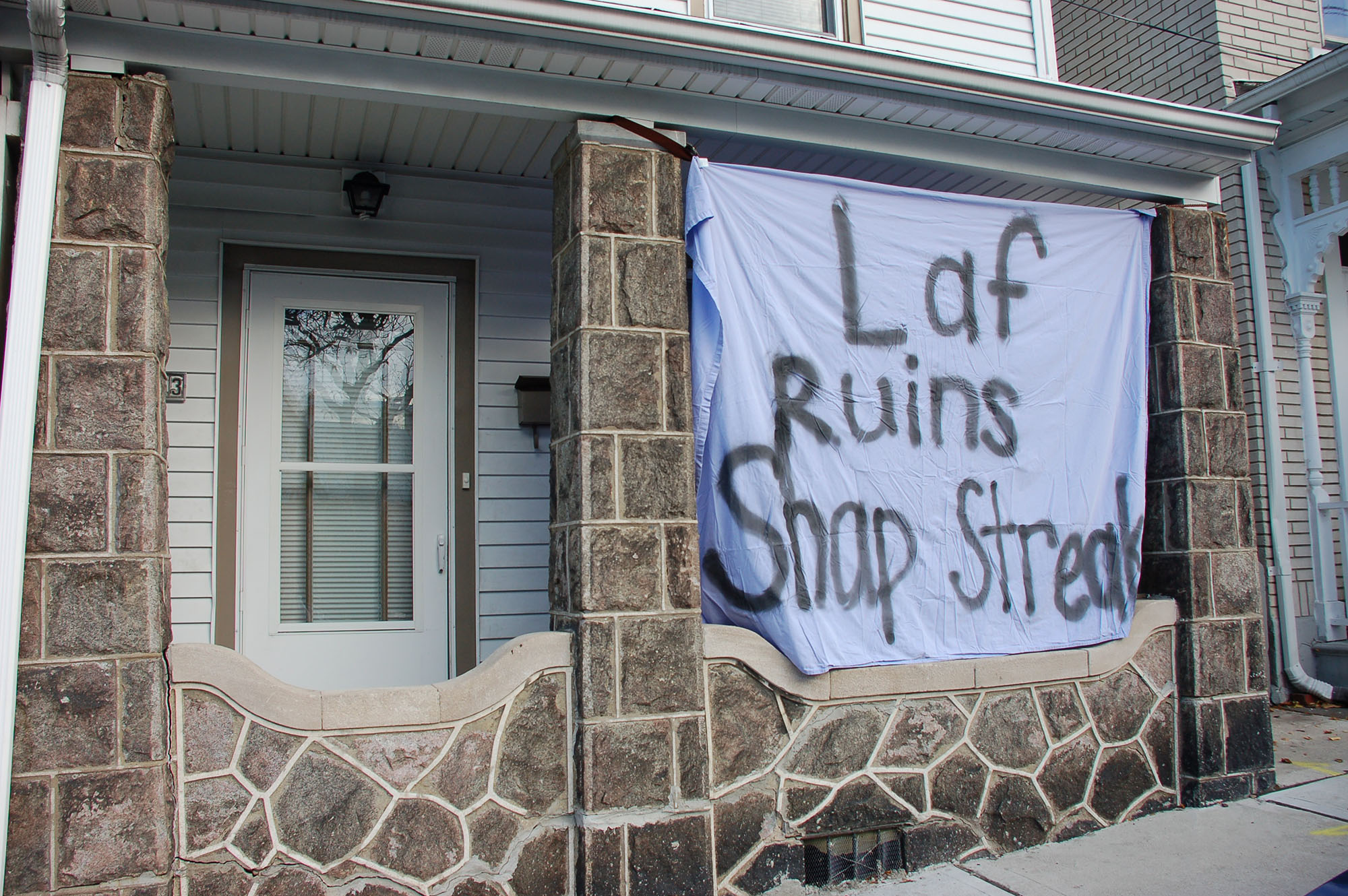"A sign reading ""Laf ruins snap streak"" hangs on a house on Webster Street on Nov. 15, 2016. Spray-painted sheets can be seen displayed on houses up and down Webster Street. (Samantha Tomaszewski/B&W Staff)"