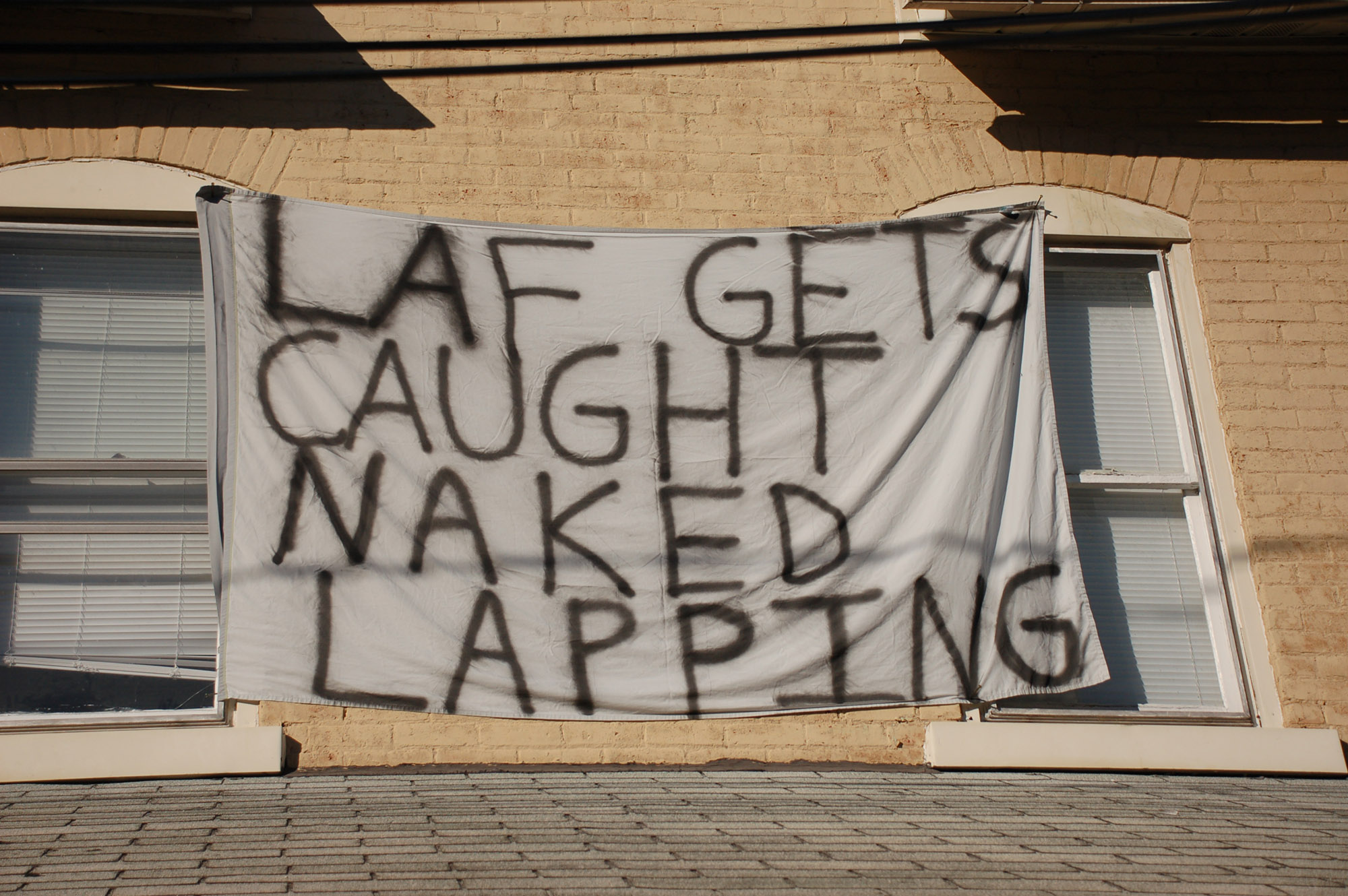 "A sign reading ""Laf gets caught naked lapping"" hangs on a house at East Fifth Street on Nov. 18, 2016. These signs are hung on the fronts of many houses on East Fifth. (Gaby Morera/B&W Staff)"