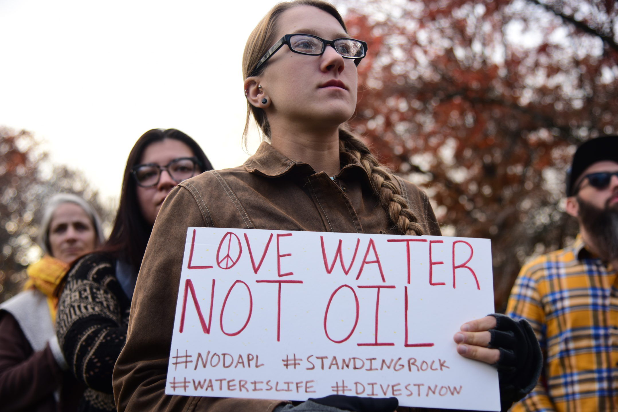 "Protester holds up sign. It reads,""Love water not oil."" (Ashley Omoma/B&W Staff)"