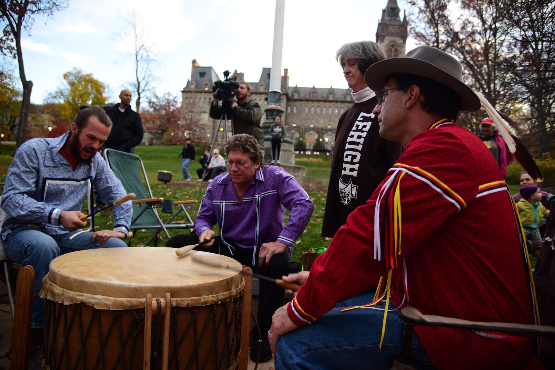 (From left) Dan Hunter, Rob Aptaker, grandmother Shirley Khabbaz and Dar Khabbaz gather around the drum. The drummers are traditionally positioned around the drum.  Usually, the men sit at the drum and the women stand singing the higher notes that strengthen the prayer or intent of the song. (Ashley Omoma/B&W Staff)