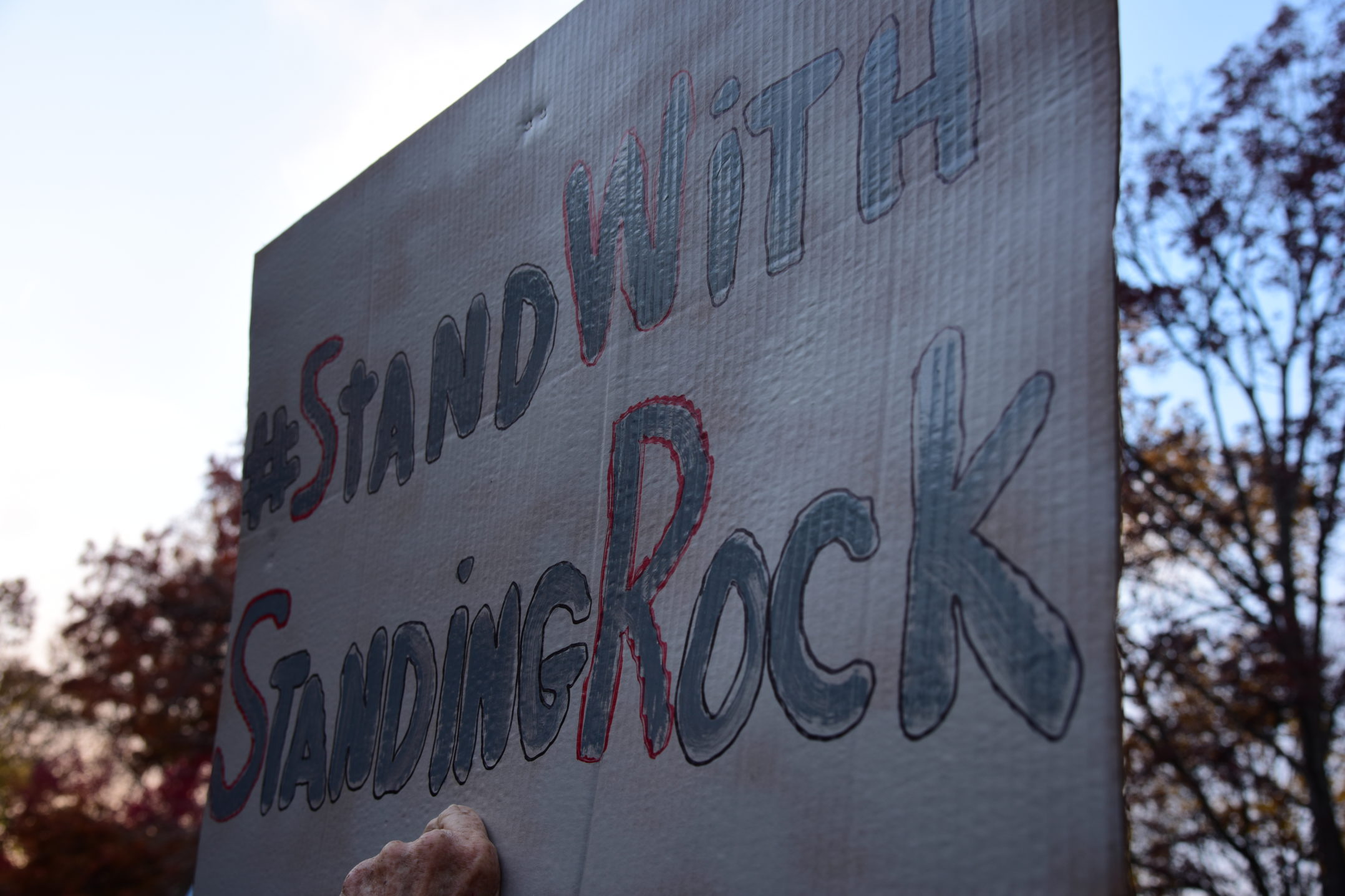 "A sign held up by protester at rally. The sign reads  ""#Standwithstandingrock."" (Ashley Omoma/B&W Staff)"