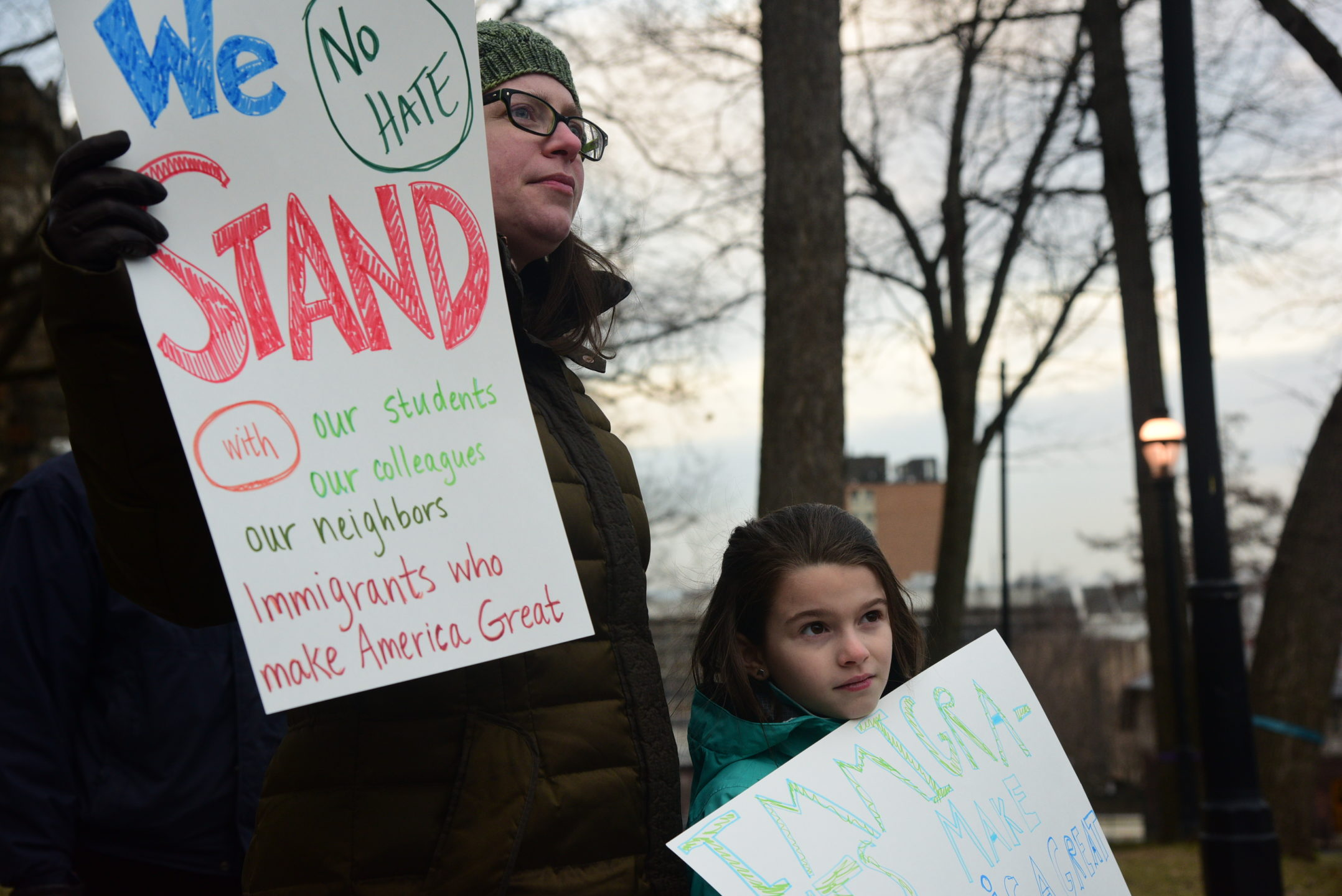 "Susan Edwards, faculty director of humanities, attends the rally with her daughter, Matilda. Edward's sign reads, ""We stand with our students, our colleagues, our neighbors. Immigrants who make America great again.""(Ashley Omoma/B&W Staff)"