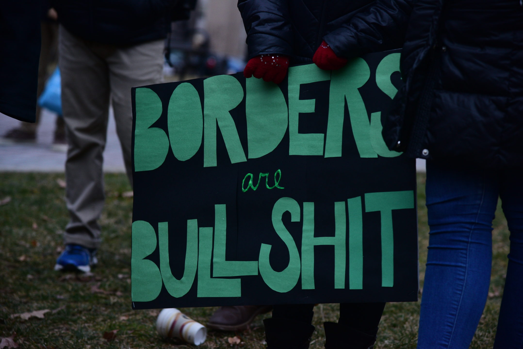 "Mikaila Skaroff, '17, and Katy Traut, '17, hold a sign they created at the rally. The sign reads, ""Borders are bullshit."" (Ashley Omoma/B&W Staff)"