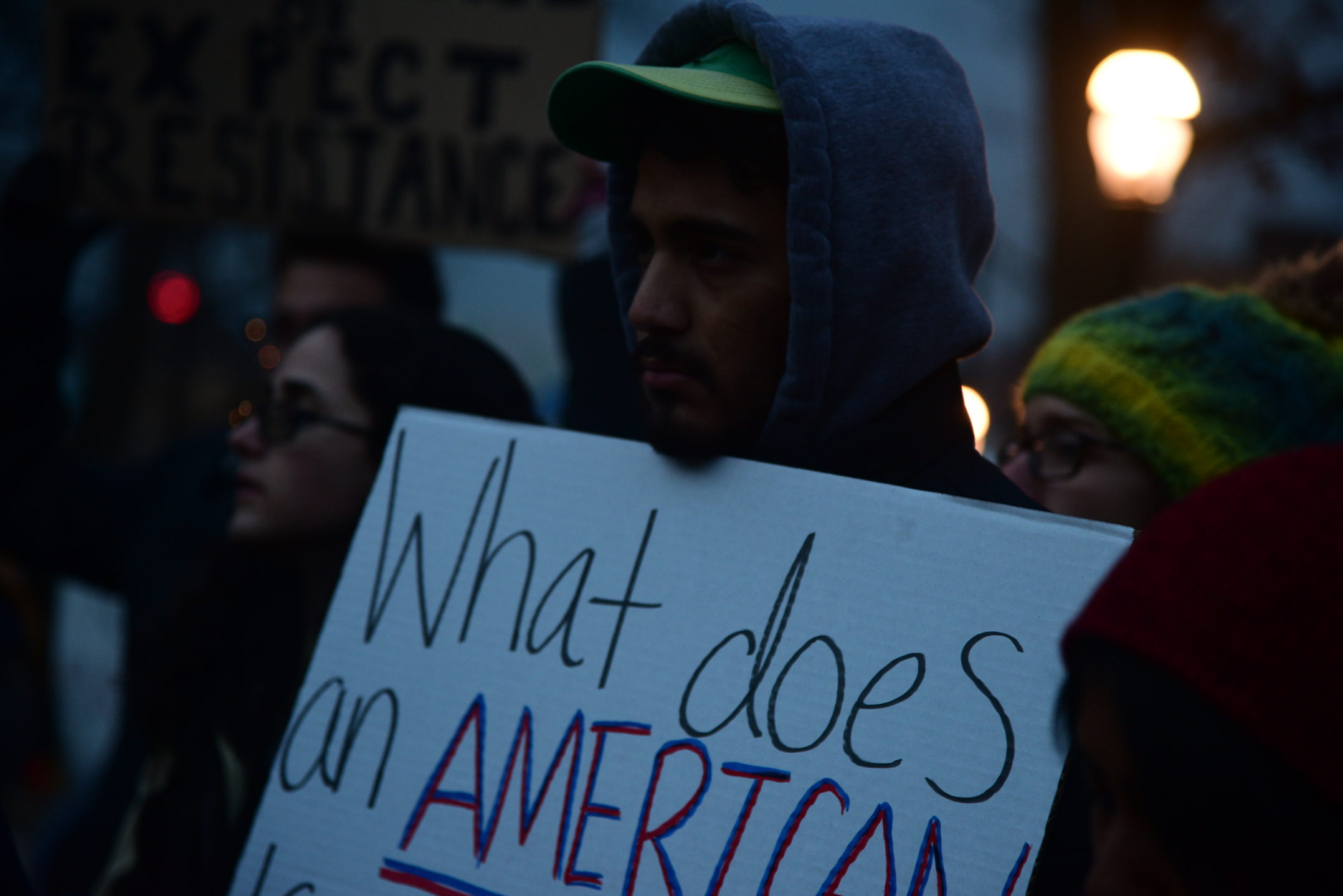 "Daniel Dalomeque, '20, holds up sign. His sign reads, ""What does an American look like?"" (Ashley Omoma/B&W Staff)"