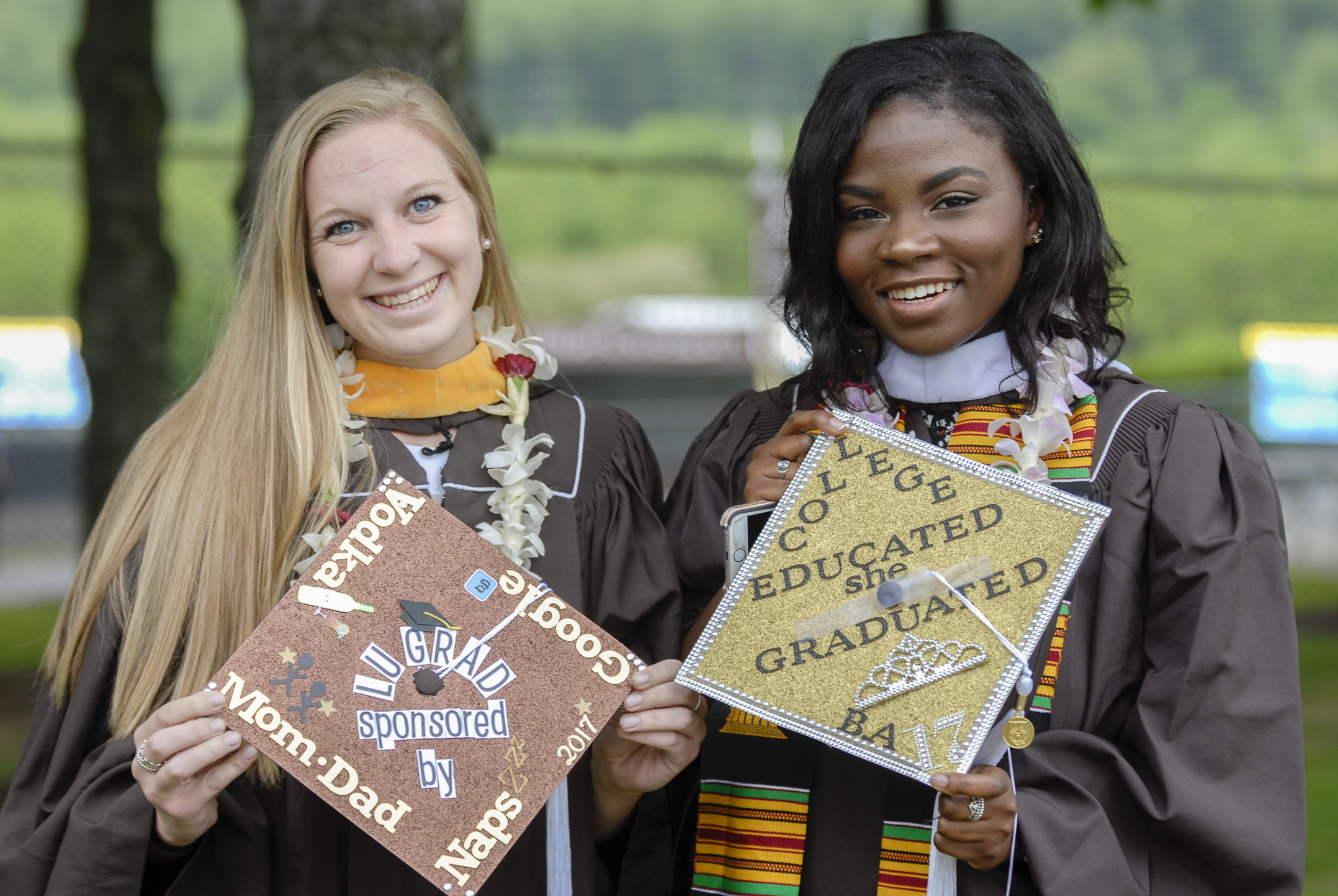 Emilee Strange, '17, left, and Aminat Ologunebi, '17, hold their decorated graduation hats Monday, May 22, 2017, outside Goodman Stadium. Strange is graduating with a degree in biology, while Ologunebi is graduating with a degree in journalism and science writing. (Roshan Giyanani/B&W Staff)