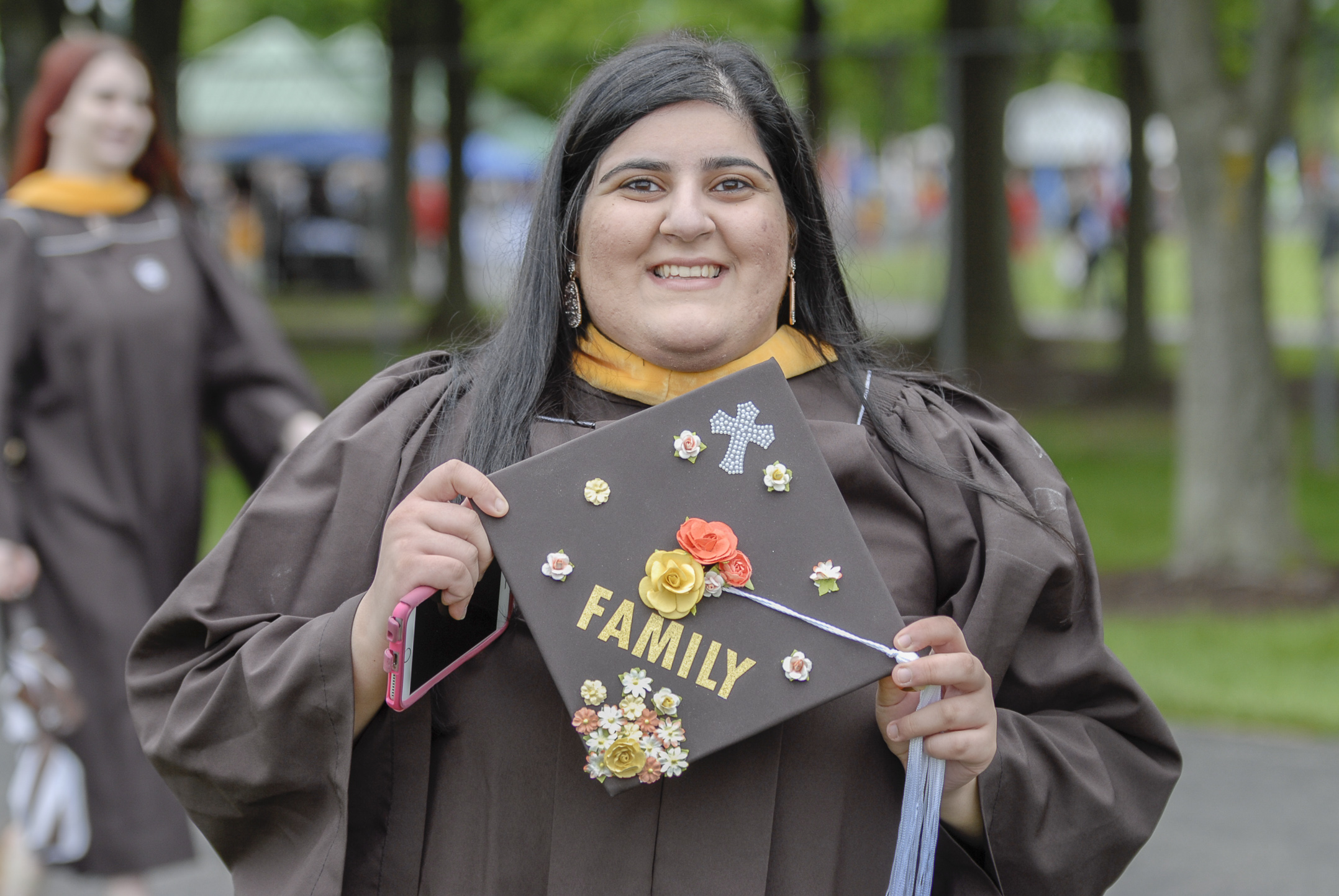 Reem Azar, '17, holds her graduation cap Monday, May 22, 2017, outside Goodman Stadium. Azar, a behavioral neuroscience graduate, decorated her cap to represent the importance of family in her life. (Roshan Giyanani/B&W Staff)