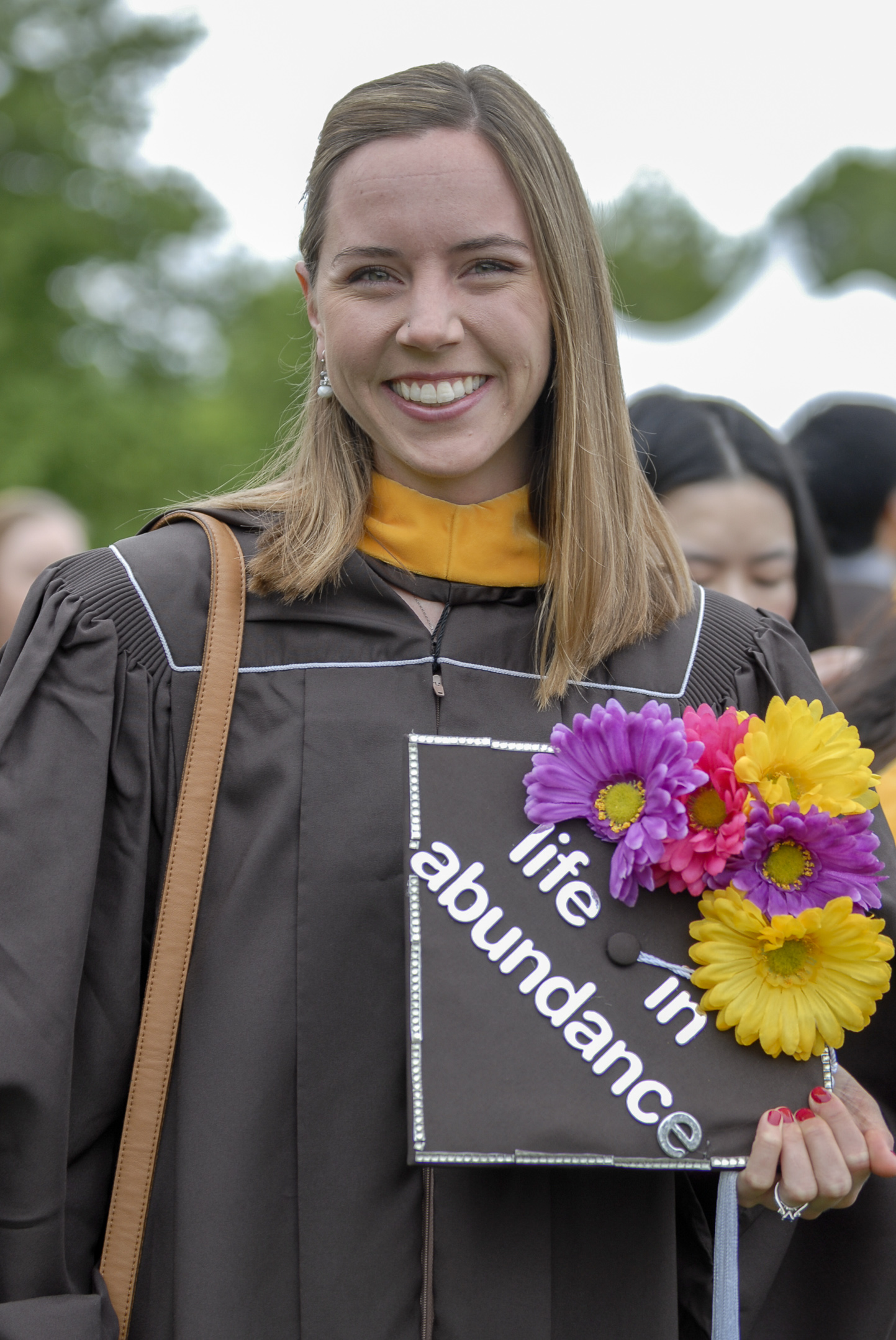 "Kendall Wilkins, '17G, holds her graduation cap Monday, May 22, 2017, outside Goodman Stadium. Wilkins, who graduated with a master's degree in economics, decorated her hat with the words ""life in abundance"" to counter the definition of economics as a way to allocate limited resources. (Roshan Giyanani/B&W Staff)"