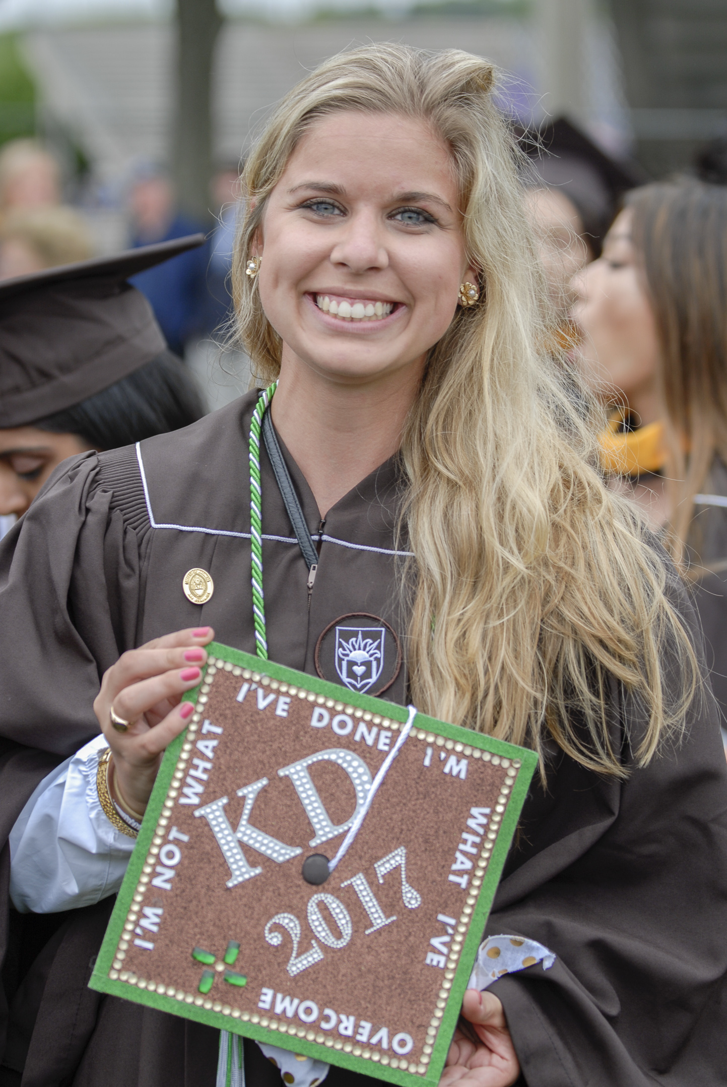 "Megan Matthews, '17, holds her graduation cap Monday, May 22, 2017, outside Goodman Stadium. Matthews is graduating with a degree in management and marketing. Matthews' cap includes the letters of her sorority, Kappa Delta, and the quote, ""I'm not what I've done, I'm what I've overcome"" to represent the challenges she's faced at Lehigh. (Roshan Giyanani/B&W Staff)"
