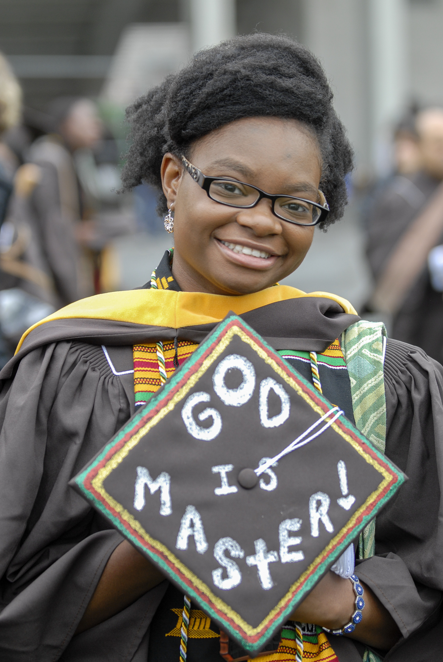 "Ornella Ngounou, '17G, holds her graduation cap, decorated with the colors of Cameroon, her home country, on Monday, May 22, 2017, outside Goodman Stadium. Ngounou graduated with a master's in business management and included the words ""God is Master!"" because for her, ""God is master of my life."" (Roshan Giyanani/B&W Staff)"