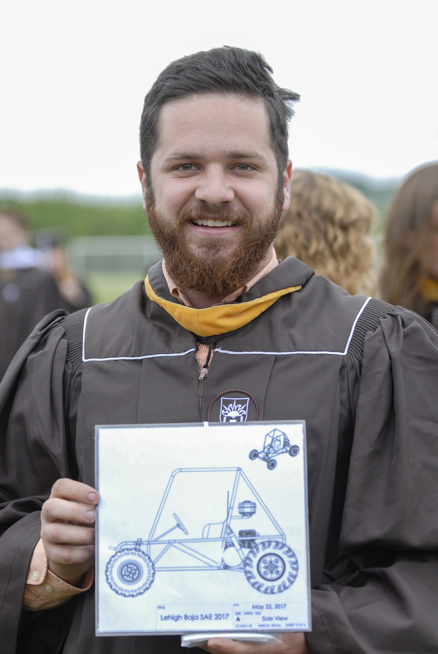 Harry Ambler, '17, a member of the Baja Society of Automotive Engineers, holds his graduation cap decorated with the schematics of the Baja team's car on Monday, May 22, 2017, outside Goodman Stadium. Ambler graduated with a degree in mechanical engineering with an aerospace minor. (Roshan Giyanani/B&W Staff)