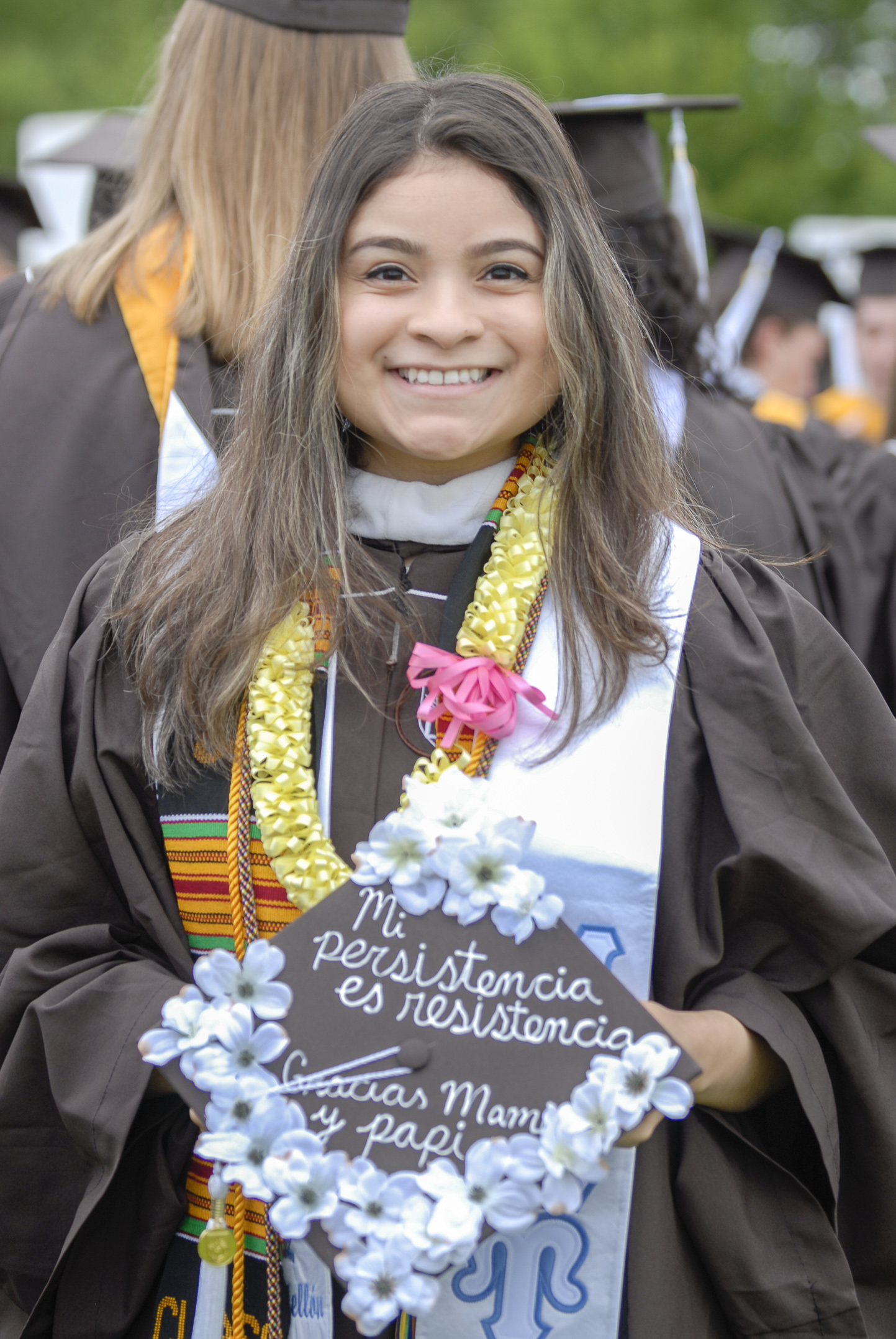 "Gladys Castellon, '17, a philosophy graduate, holds her graduation cap Monday, May 22, 2017, outside Goodman Stadium. Castellon's cap said, ""My persistence is my resistance"" and ""Thank you Mom and Dad"" in Spanish. (Roshan Giyanani/B&W Staff)"