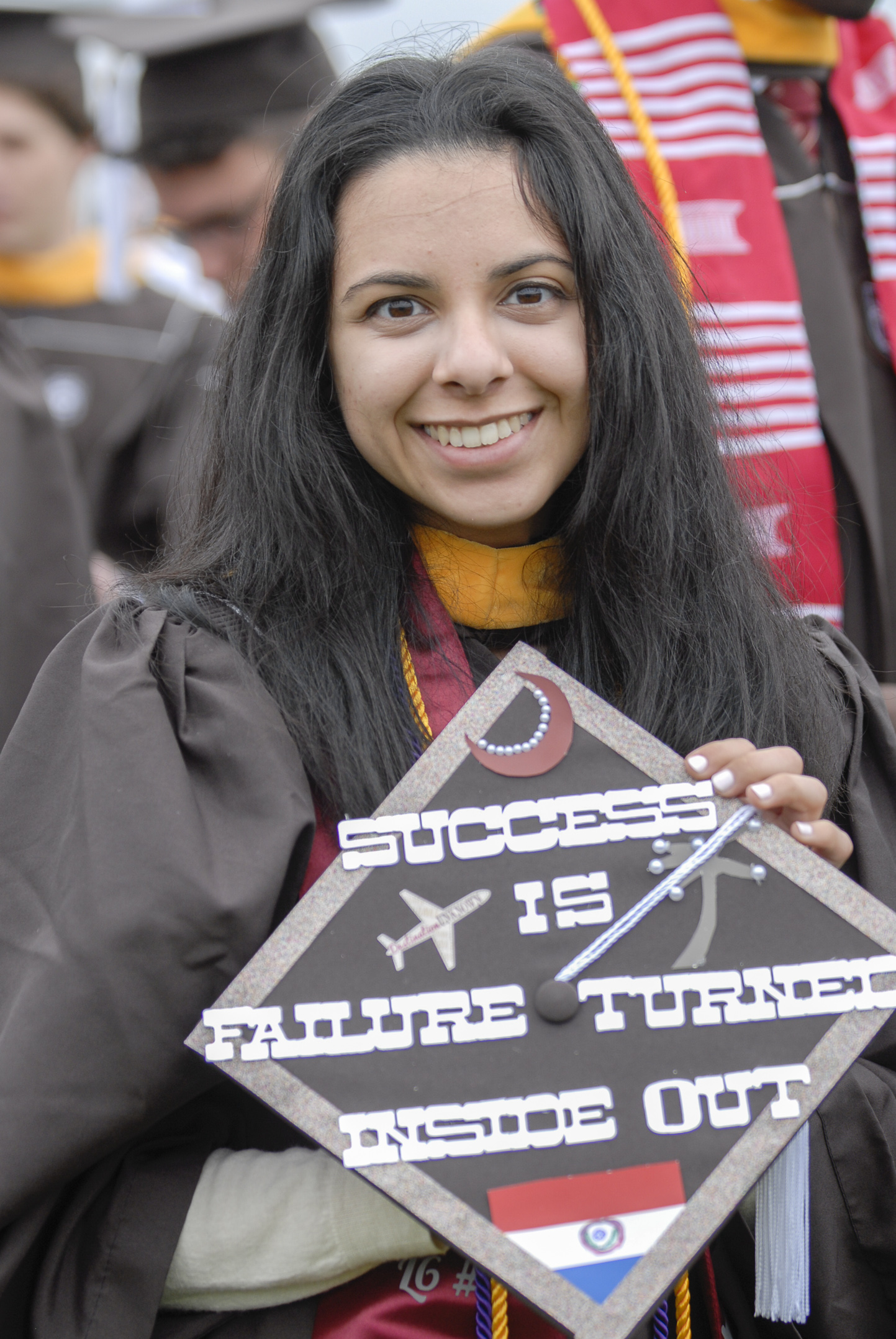 "Alejandra Silguero, '17, holds her graduation cap Monday, May 22, 2017, outside Goodman Stadium. A business information systems graduate, Silguero's hat features a moon to represent her sorority, the flag of Paraguay and a line from the poem ""Don't Quit."" (Roshan Giyanani/B&W Staff)"