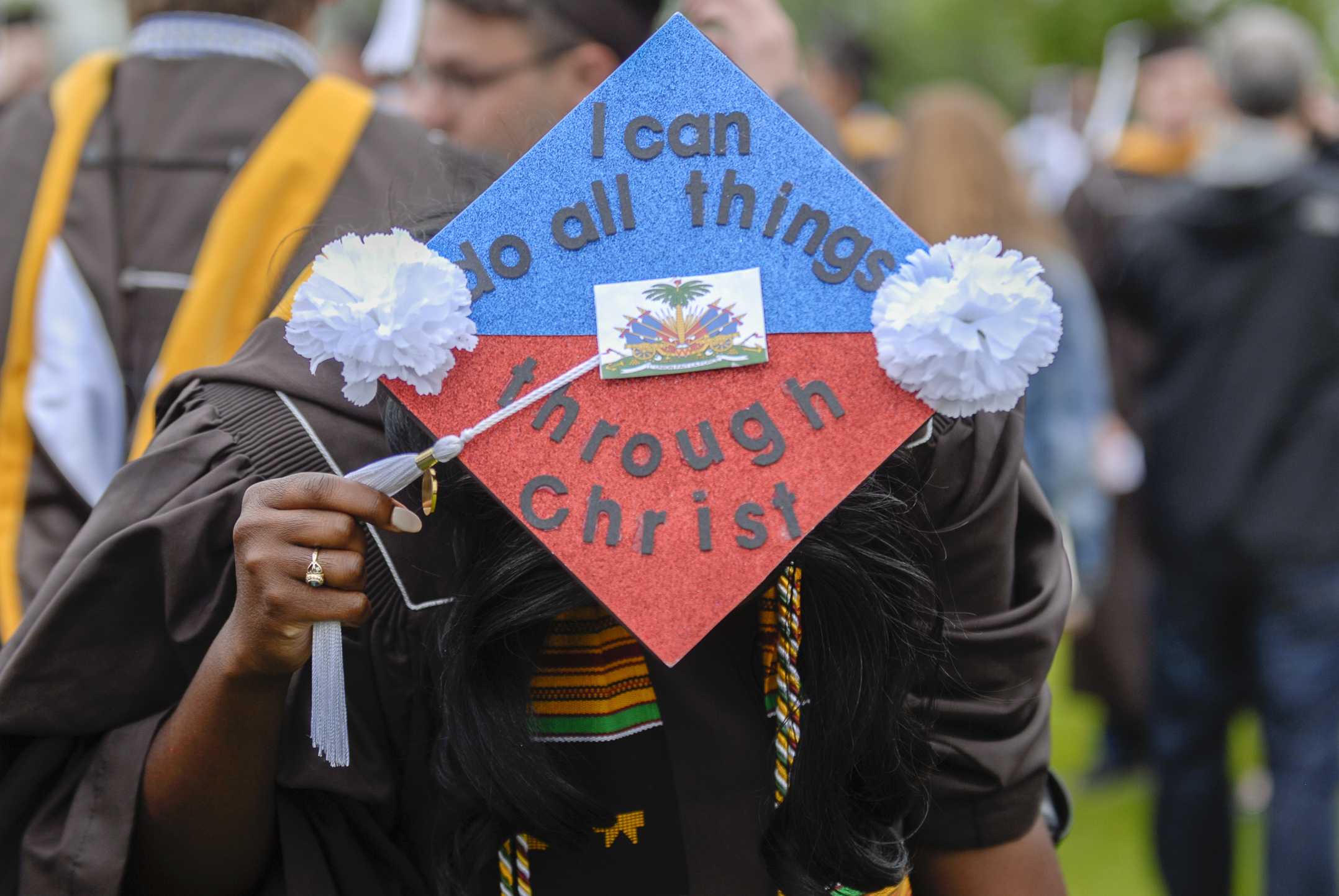 Esther Petit-Frere, '17, a finance graduate, shows her decorated graduation cap Monday, May 23, 2017, outside Goodman Stadium. Petit-Frere decorated her hat to signify her home country, Haiti, and included a Bible verse that she said got her through college. (Roshan Giyanani/B&W Staff)