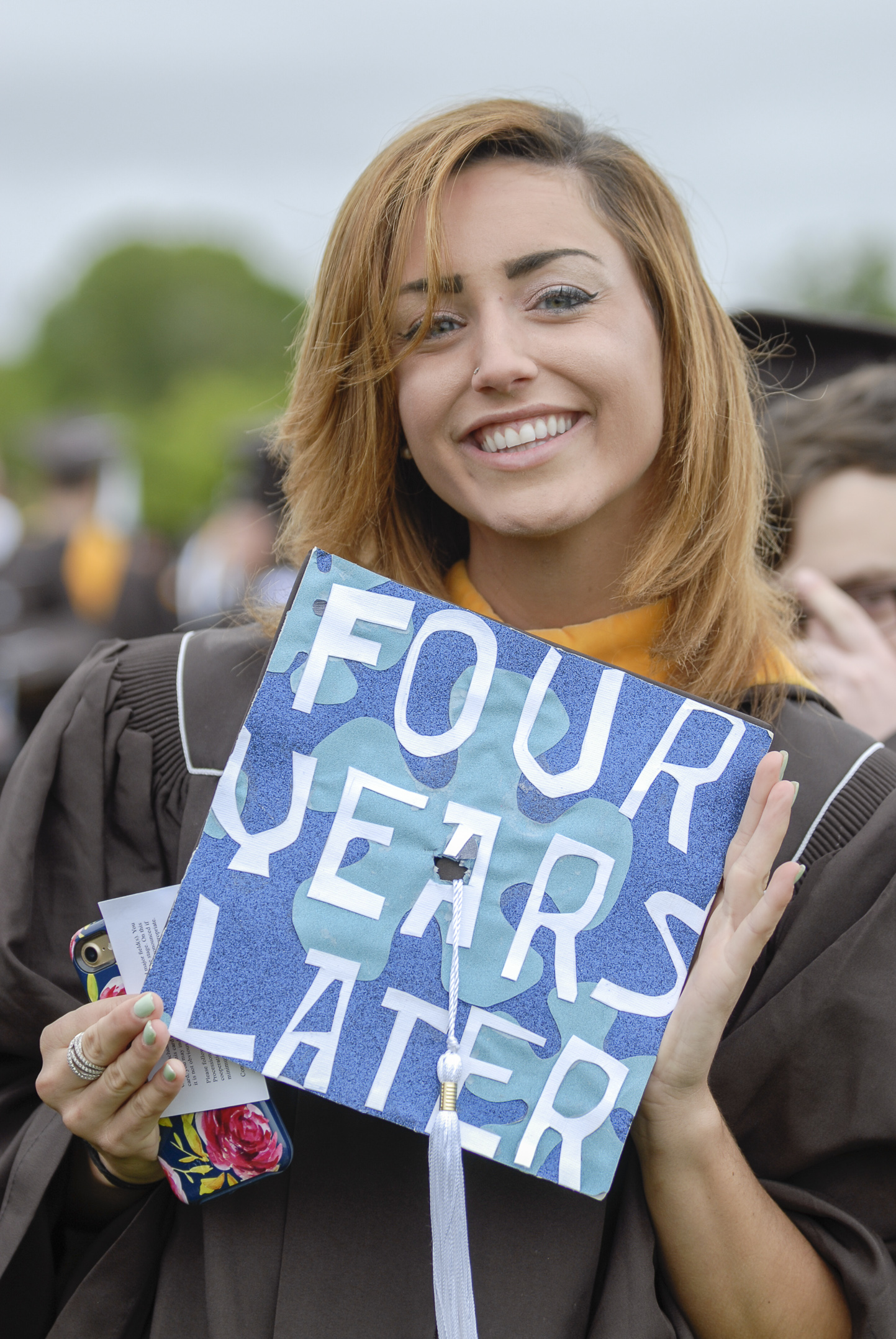 "Ceara Hogan, '17, an earth and environmental science graduate, holds her cap Monday, May 22, 2017, outside Goodman Stadium. Hogan decorated her hat with the words ""four years later"" as a reference to SpongeBob and the four years it took to get her degree. (Roshan Giyanani/B&W Staff)"