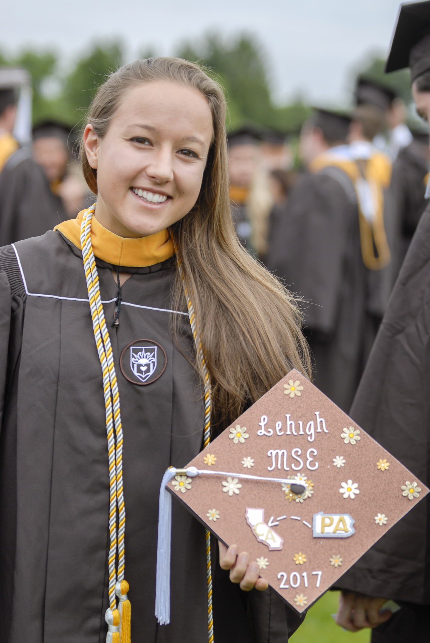 Amanda Leigh Ruschel, '17, holds her graduation cap Monday, May 22, 2017, outside Goodman Stadium. Ruschel, a material science and engineering graduate, decorated her hat to represent her major and her upcoming job in California. (Roshan Giyanani/B&W Staff)