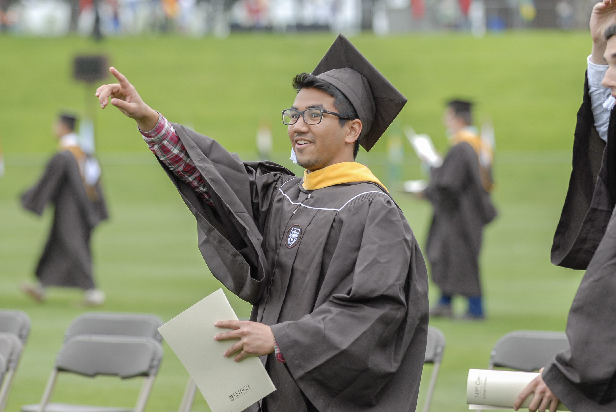 Jayesh Chokshi, '17, points to the audience Monday, May 22, 2017, in Goodman Stadium. Chokshi is a materials science and engineering graduate. (Roshan Giyanani/B&W Staff)