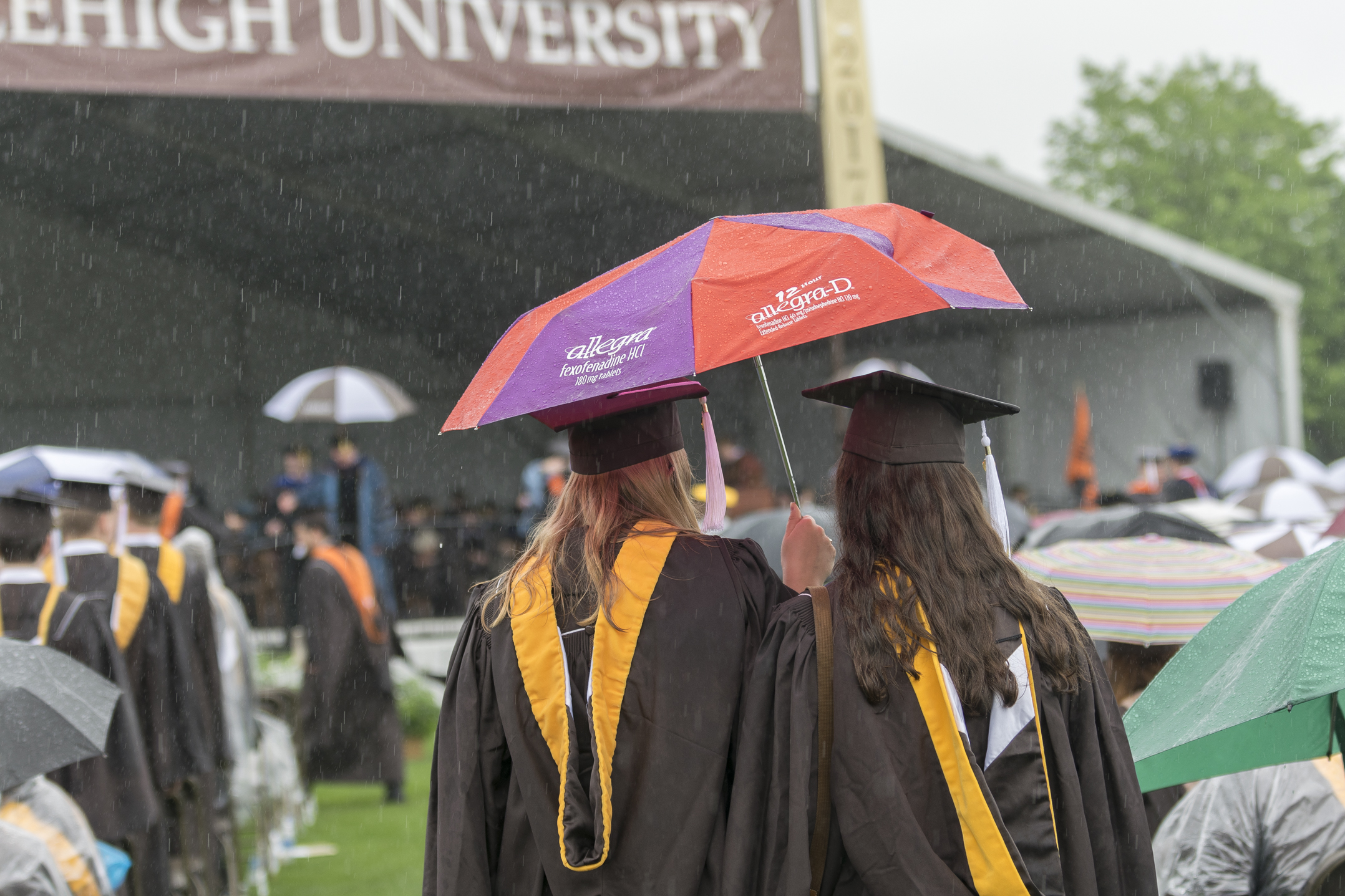 Two students huddle under an umbrella during commencement Monday, May 22, 2017, in Goodman Stadium. The rain began after Stephanie Ruhle's commencement address and slowed down toward the end of the ceremony. (Roshan Giyanani/B&W Staff)