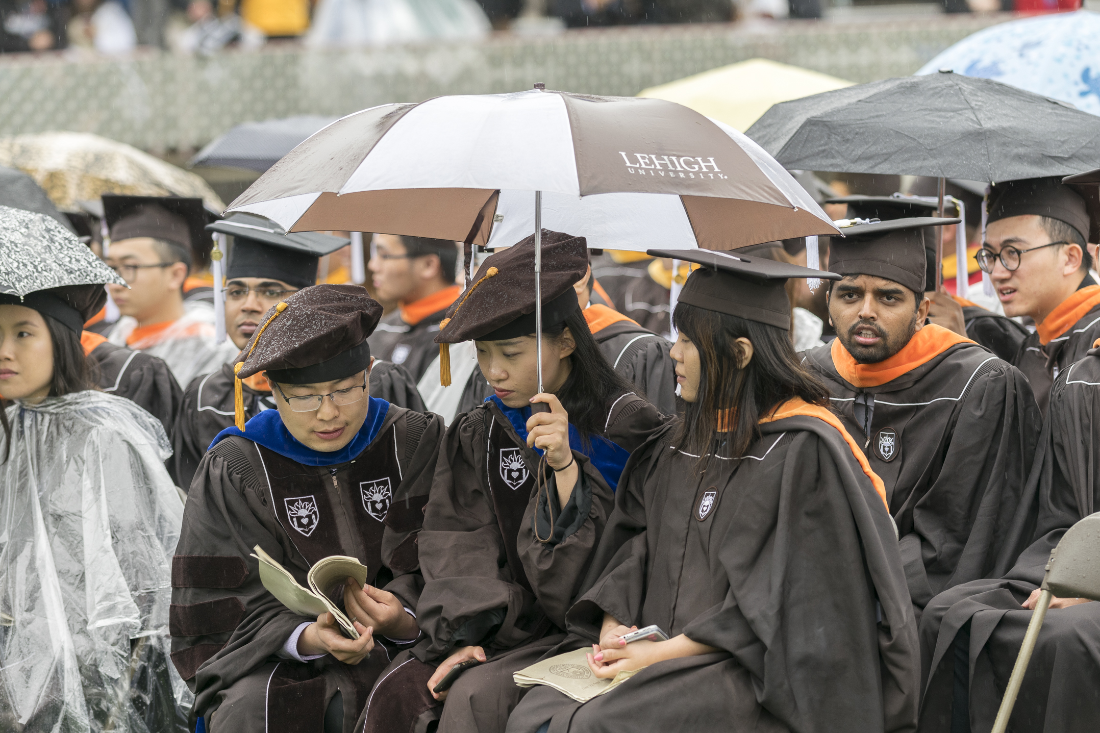 Students use an umbrella to block the rain while flipping through the program Monday, May 22, 2017, in Goodman Stadium. Most students and visitors huddled under umbrellas or ponchos for protection from the inclement weather. (Roshan Giyanani/B&W Staff)