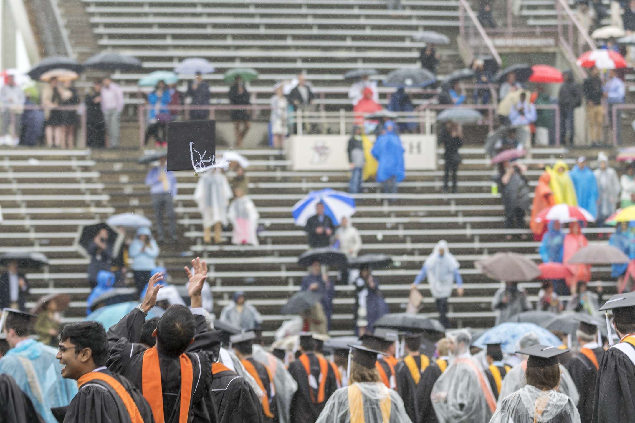 A student throws his cap in the air after commencement ends Monday, May 22, 2017, in Goodman Stadium. Many students decorated their caps to reflect their interests or honor their home countries. (Roshan Giyanani/B&W Staff)
