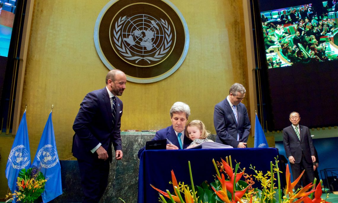 Former U.S. Secretary of State John Kerry with his two-year-old granddaughter Isabelle Dobbs Higginson on his lap and United Nations Secretary General Ban ki Moon looking on signs the COP21 Climate Change Agreement on behalf of the United States during