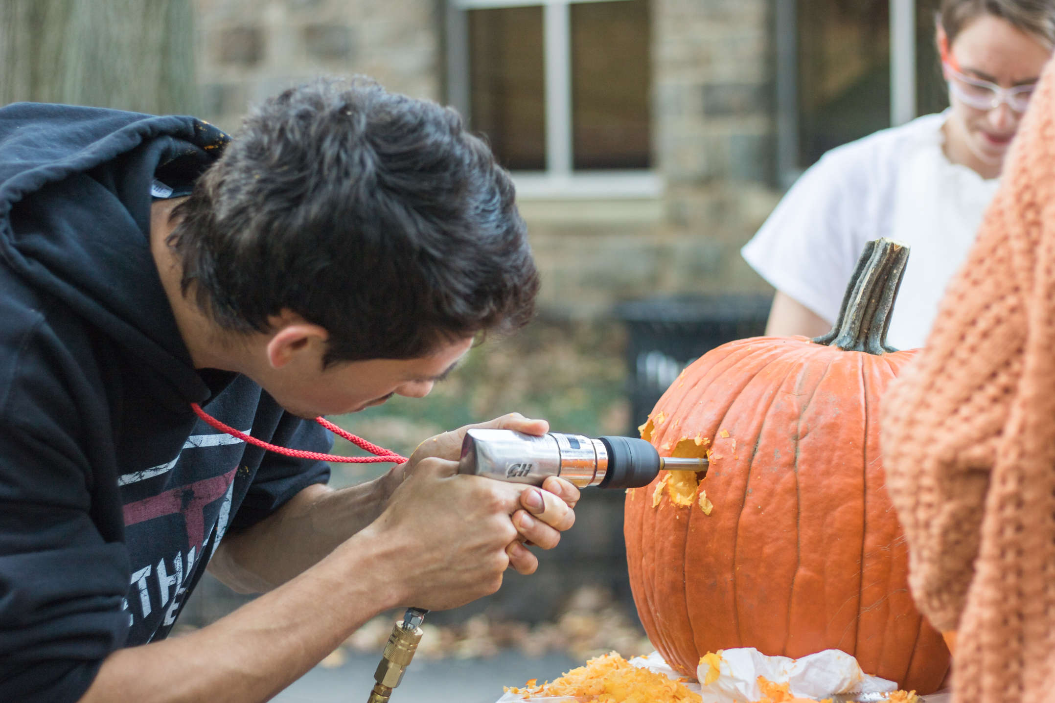 Sam Joynson, '18, uses a power tool to make holes in his pumpkin Oct. 27 outside of Wilbur Powerhouse. The event was led by the Wilbur Powerhouse team as part of the MakeX series. (Sam Henry/B&W Staff)
