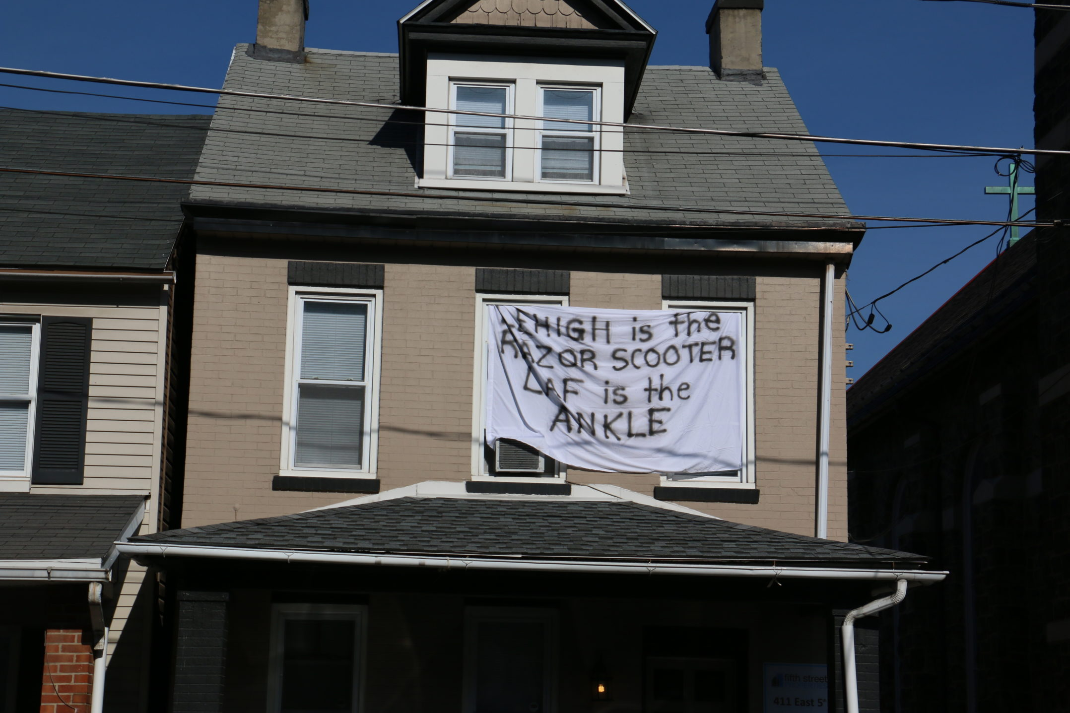 "A sign reading ""Lehigh is the Razor scooter, Laf is the ankle"" hangs outside a house on E. Fifth Street on Wednesday, Nov. 15, 2017. Many Lehigh students hang signs outside of their homes poking fun at Lafayette. (Parker Hentz/B&W Staff)"