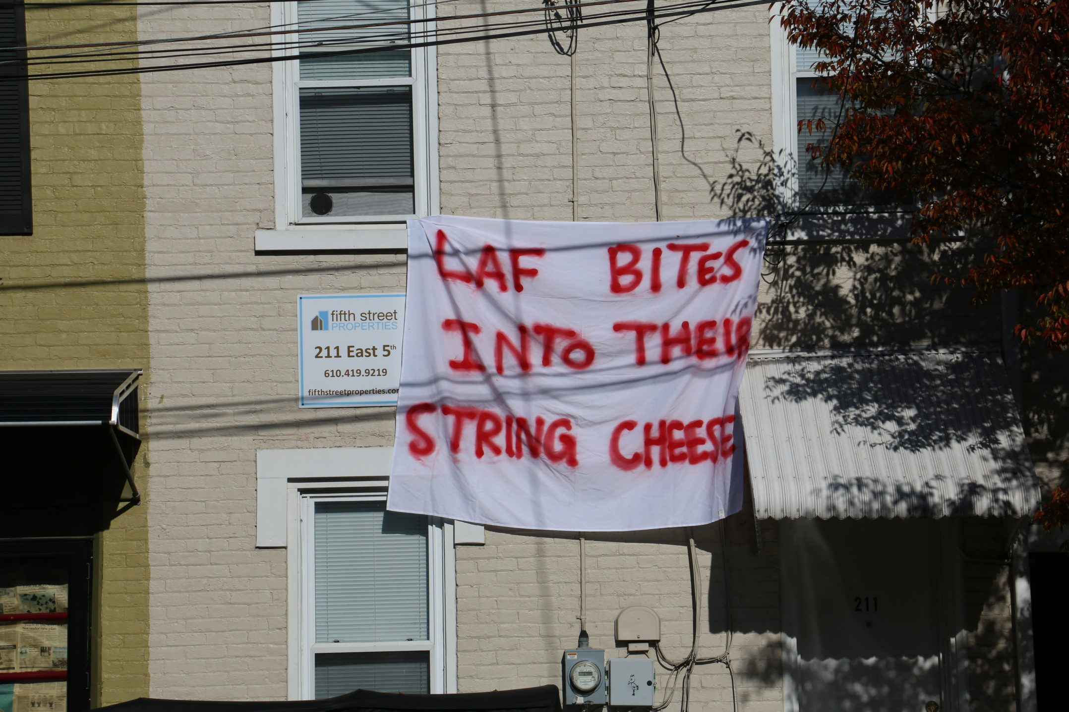 "A sign reading ""Laf bites into their string cheese"" hangs from a home on E. Fifth Street on Wednesday, Nov. 15, 2017. Other Le-Laf traditions include bed races and the slow burn bonfire. (Parker Hentz/B&W Staff)"